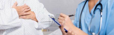 Photo pour Vue recadrée d'une femme âgée touchant la poitrine alors qu'elle souffrait d'une crise de souffle près d'une infirmière écrivant sur un presse-papiers, avant-plan flou, bannière - image libre de droit