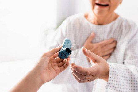 cropped view of nurse giving inhaler to aged woman suffering from asthma attack on blurred background