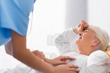 infirmière toucher une femme âgée souffrant de maux de tête tout en étant couché les yeux fermés, avant-plan flou