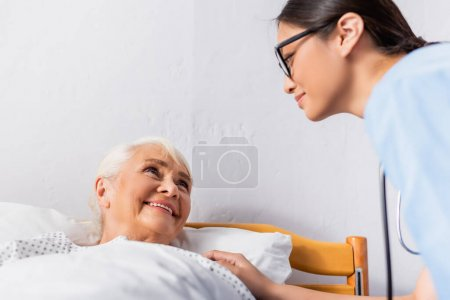 Photo pour Jeune infirmière asiatique regardant sourire femme âgée couché à l'hôpital - image libre de droit