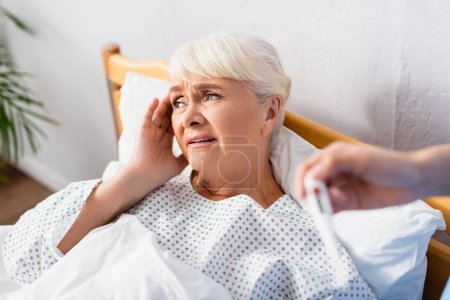 nurse holding thermometer near sick senior woman suffering from headache, blurred foreground