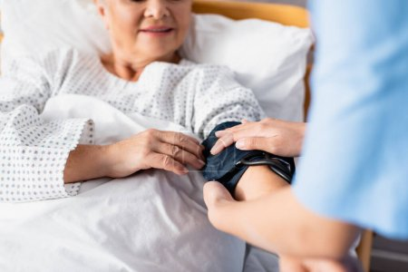 Photo for Cropped view of nurse fixing cuff of tonometer on arm of elderly woman, selective focus - Royalty Free Image