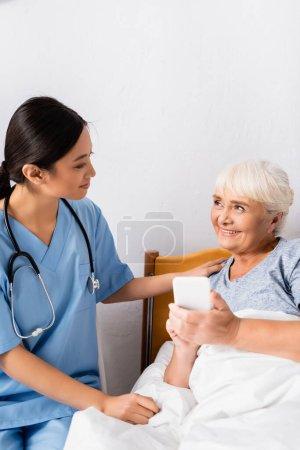glückliche ältere Frau schaut lächelnde asiatische Krankenschwester an, während sie Smartphone mit leerem Bildschirm hält