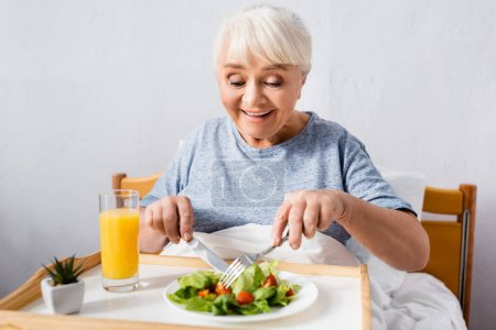 pleased senior woman having breakfast in bed on blurred foreground