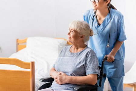 Photo for Young nurse near smiling aged woman sitting in wheelchair and looking away - Royalty Free Image