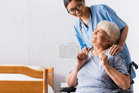 Photo for Happy asian nurse touching shoulders of aged handicapped woman laughing in wheelchair - Royalty Free Image