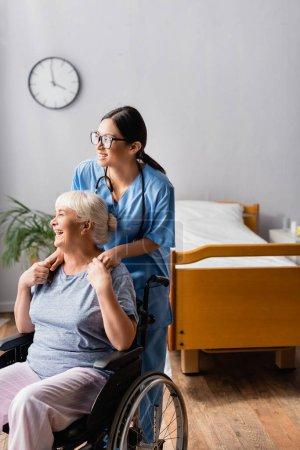 fröhliche, behinderte Seniorin lacht, während sie die Hände einer jungen asiatischen Krankenschwester berührt