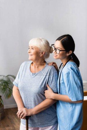 glückliche alte Frau mit Gehstock und junge asiatische Krankenschwester lächelt und schaut im Krankenhaus weg