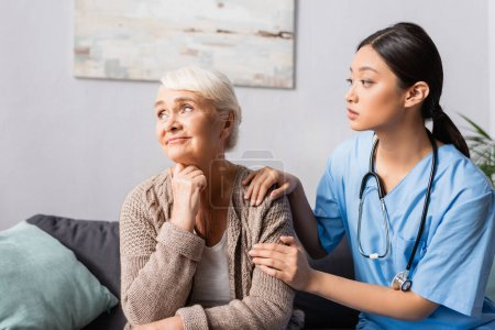 Photo for Young asian nurse calming upset elderly woman sitting and looking away in nursing home - Royalty Free Image