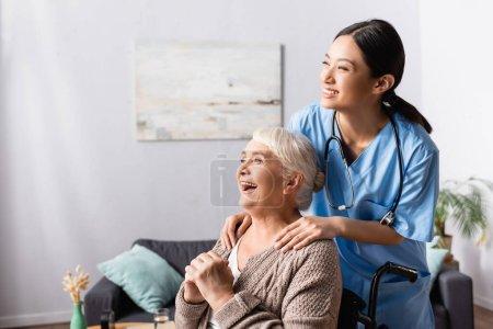 glücklich asiatische Krankenschwester berührt Schultern der alten behinderten Frau lachen im Rollstuhl