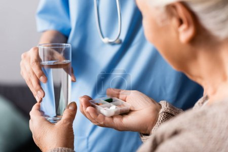 partial view of nurse giving pills and glass of water to elderly woman, selective focus