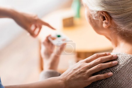Photo for Partial view of nurse touching shoulder of aged woman and pointing with finger at pills on blurred background - Royalty Free Image