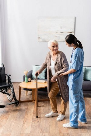 positive elderly woman with walking stick looking at asian nurse supporting her in nursery home