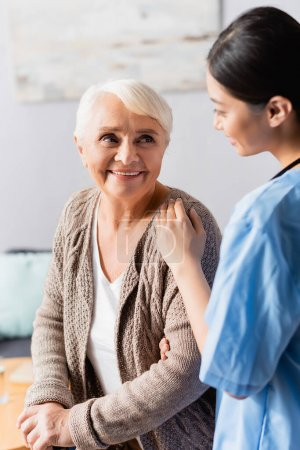 young asian nurse touching shoulder of smiling senior woman in nursing home, blurred foreground