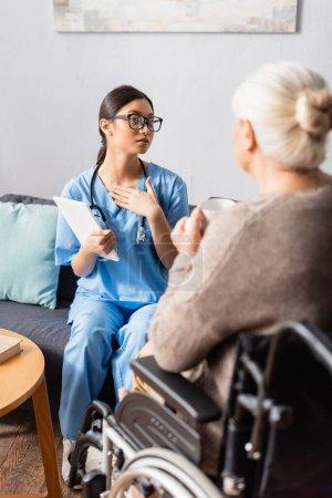 junge Asiatin berührt Brust, während sie mit alter behinderter Frau spricht, die im Rollstuhl auf verschwommenem Vordergrund sitzt
