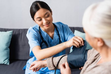 Photo for Young asian nurse fixing cuff of tonometer on arm of aged woman in hospital - Royalty Free Image