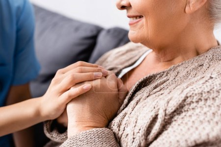 cropped view of nurse touching hands of happy elderly woman in nursing home