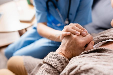 partial view of nurse touching hands of aged patient in nursing home, blurred background