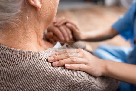 abgeschnittene Ansicht der Krankenschwester, die Hand und Schulter einer älteren Patientin im Pflegeheim berührt, verschwommener Hintergrund