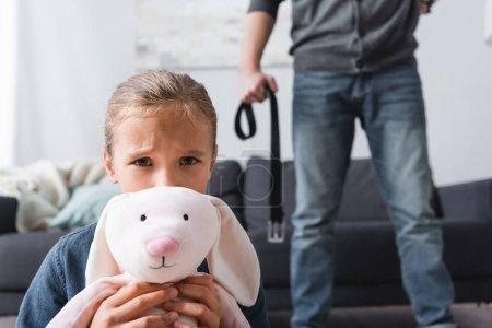 Verängstigtes Mädchen mit Stofftier, das in die Kamera schaut, in der Nähe eines missbräuchlichen Vaters mit Gürtel auf verschwommenem Hintergrund
