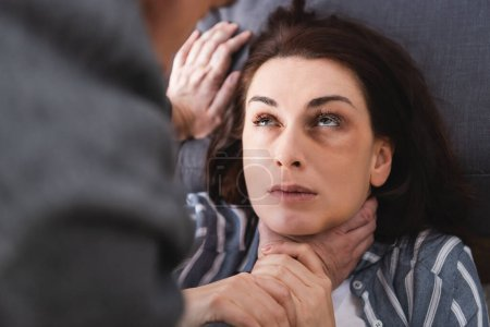 Photo for Suffocating woman with bruises on face near abusive husband on blurred foreground - Royalty Free Image