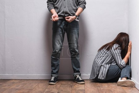 Photo pour Abuseur décoller ceinture près de la femme avec ecchymose sur la main assis sur le sol à côté des murs - image libre de droit