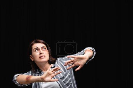 Photo pour Victime effrayée de violence domestique ne montrant aucun geste isolé sur noir - image libre de droit