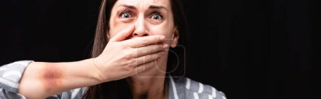 Scared victim of domestic abuse covering mouth isolated on black, banner