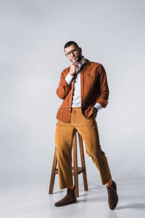 Photo for Fashionable man with hand in pocket of pants looking at camera near chair on grey background - Royalty Free Image