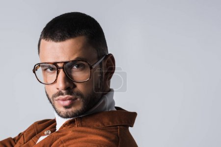 Portrait of young man in eyeglasses looking at camera isolated on grey