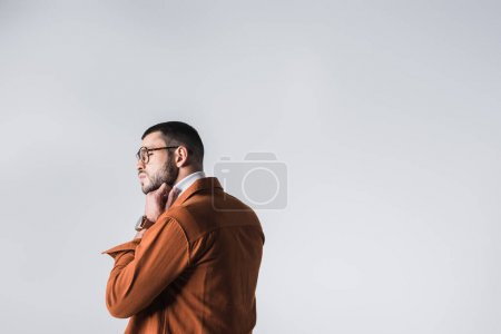 Photo for Bearded man in eyeglasses adjusting turtleneck isolated on grey - Royalty Free Image