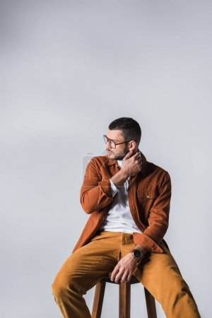 Photo for Young man in casual clothes and eyeglasses looking away on chair isolated on grey - Royalty Free Image