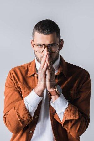 Photo pour Homme élégant dans des lunettes avec des mains de prière regardant la caméra isolée sur gris - image libre de droit