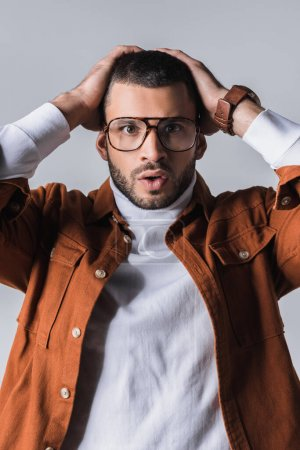 Excited stylish man in eyeglasses looking at camera isolated on grey