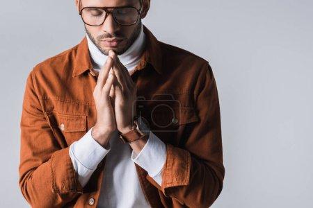 Photo pour Homme élégant avec les yeux fermés montrant les mains priantes isolées sur gris - image libre de droit