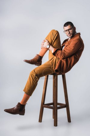 Photo for Stylish man in brown shoes and terracotta jacket looking at camera on chair on grey background - Royalty Free Image