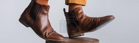 Photo pour Vue recadrée de l'homme en chaussures marron debout sur une chaise isolée sur gris, bannière - image libre de droit