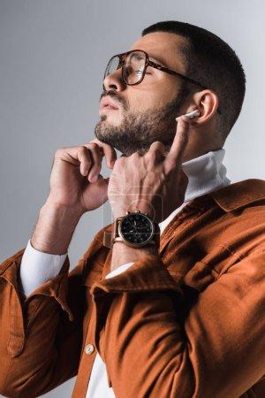 Photo pour Homme élégant ajustant écouteur sur fond gris - image libre de droit