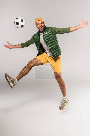 Positive man jumping near football in air on grey background