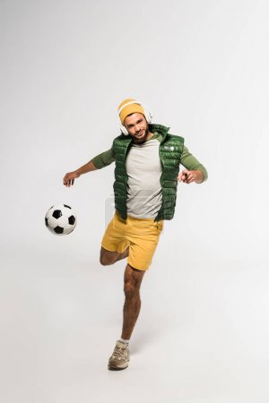 Young sportsman in headphones pointing at camera while playing football on grey background