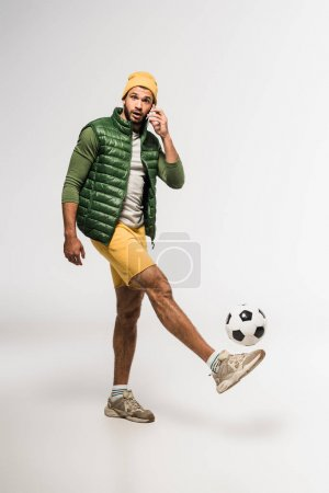 Sportif barbu parlant sur smartphone tout en jouant au football sur fond gris