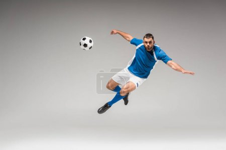 Sportsman looking at camera while jumping near football on grey background