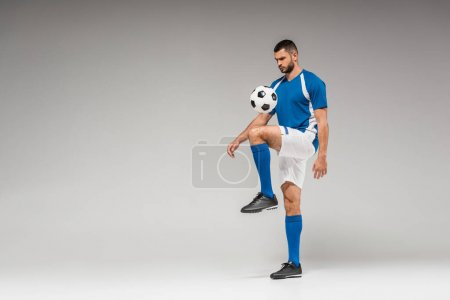 Bearded sportsman training with football on grey background