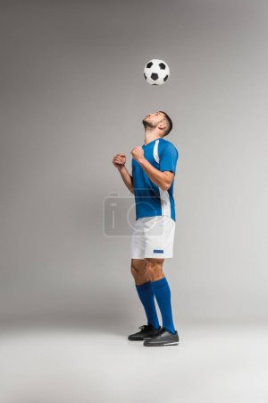 Young sportsman looking at football in air on grey background