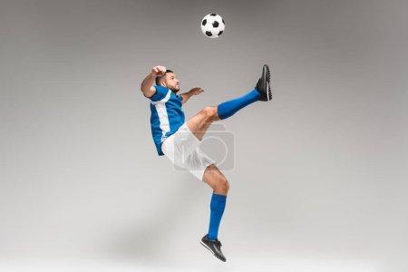 Photo pour Sportsman en chaussettes de genou et sautant de vêtements de sport tout en jouant au football sur fond gris - image libre de droit
