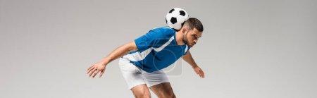 Photo pour Jeune sportif tenant le football sur le dos isolé sur gris, bannière - image libre de droit