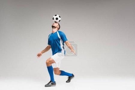 Photo pour Sportsman tenant le football sur la tête tout en équilibrant sur fond gris - image libre de droit
