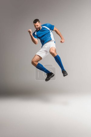 Photo for Athletic man showing yeah gesture while jumping on grey background - Royalty Free Image