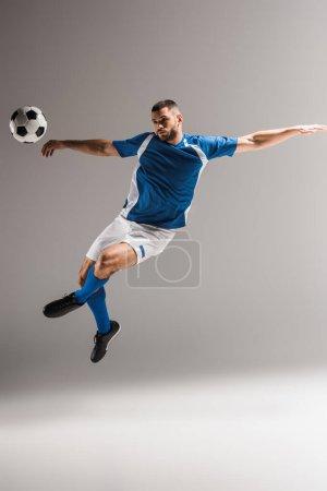 Photo pour Homme sportif sautant avec les jambes croisées près du football sur fond gris - image libre de droit