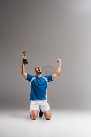 Sportsman with golden champion cup showing yeah gesture while kneeling on grey background